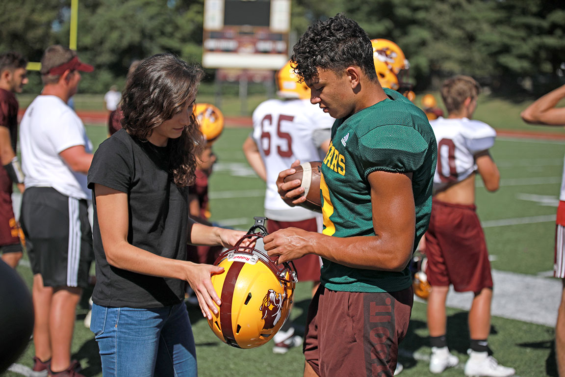 School of Public Health doctoral student Megan Huibregtse shows North player Reece Lozano the mouthguard participating students are wearing as part of the study.