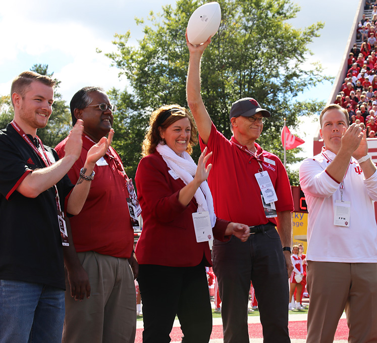 Dean Mason celebrates receiving the game ball during a football game sponsored by the School of Education
