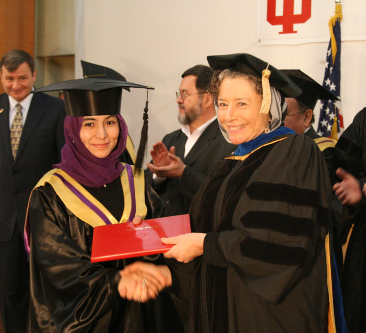 Mitzi Lewison (on right), professor of language, culture, and literacy education, congratulating an Afghan participant in the higher education program during graduation ceremonies in 2011.